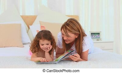 A grandmother reading a book with her grand daughter on her...