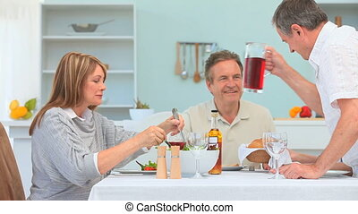 Man serving his friends strawberry cordial during the dinner