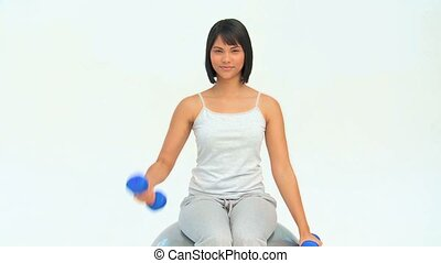 Asian woman with dumbbells on a gym ball against a white...