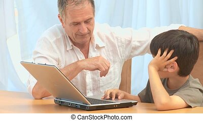 Grandfather with his grandson looking at a laptop