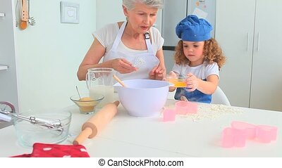 Elderly woman baking with her grand daughter in the kitchen