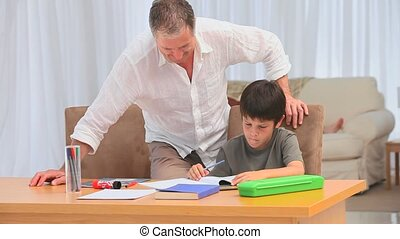Adorable boy doing his homeworks next to his grandfather in...