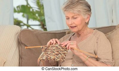 Pretty elderly woman knitting on the sofa