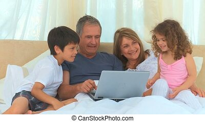 Family looking at a laptop on the grandparents bed