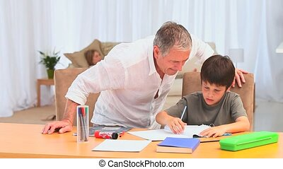 Little dark-haired boy doing homeworks after school in the...