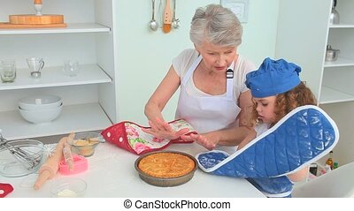Cute little girl cooking with her grandmother