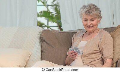 Aged woman playing cards on her couch