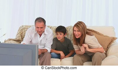 Family watching a match on tv in the living room