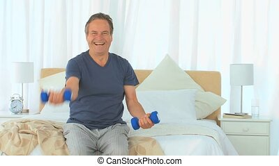 Dynamic man with dumbbells in the bedroom