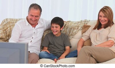 Family laughing in front of the tv in the living room