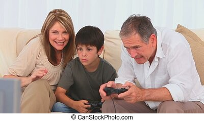 Family playing video games with two joysticks