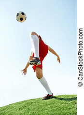 Active game - Portrait of soccer player kicking ball by knee...