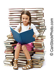 Smart reader - Portrait of diligent pupil sitting on pile of...