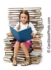 Smart reader - Portrait of diligent pupil sitting on pile of...