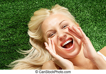 Scream - Photo of shouting female lying on green grass and...
