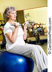 Training with barbells - Portrait of aged woman doing...