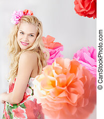 Spring time - Happy woman with pink flower in wavy hair...