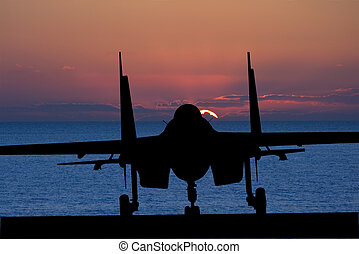 Silhouette of military attack aircraft against vibrant...