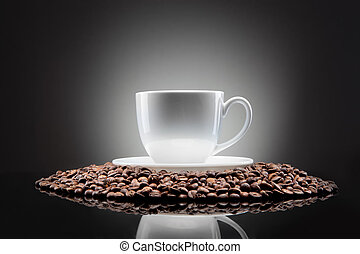 white cup with coffee beans on black