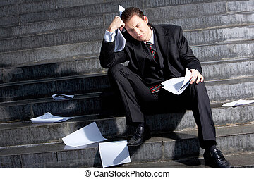 Consequences of crisis - Portrait of sad businessman sitting...