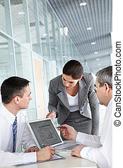 Meeting - A business team of three planning work in office