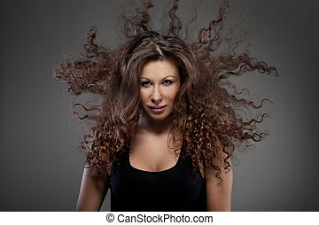 portrait of beautiful woman with curly hair in air
