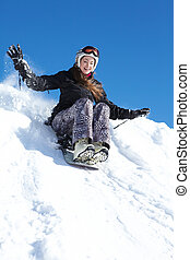 Winter fun - Portrait of happy girl riding on snowboard in...