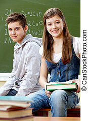 Classmates - Portrait of happy guy and girl looking at...