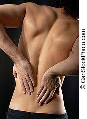 Sore back - Back view of young man touching aching back