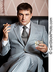Rich man - Portrait of handsome man in grey suit sitting on...