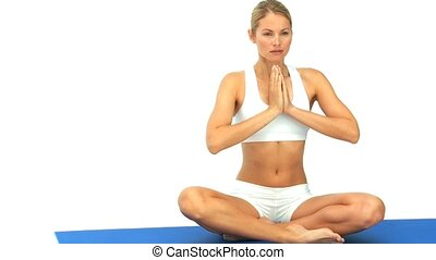 Blond woman doing yoga on a ground cloth against a white...