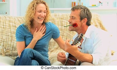 Romantic man playing guitar with a rose between the teeth