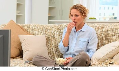 Curly-haired lady watching the tv with popcorn on her sofa