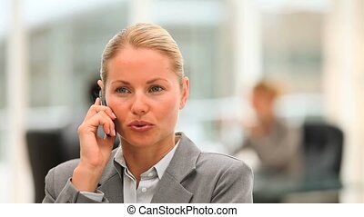 Lovely business woman speaking on the phone in her company