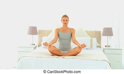 Attractive woman doing yoga on her bed