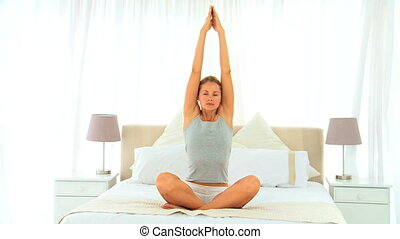 Blond lady doing exercise on her bed