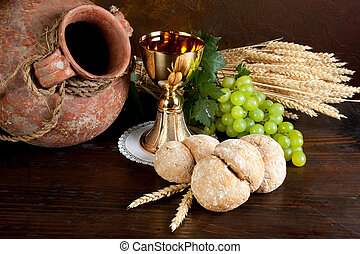 Communion wine and bread - Grapes and holy bread next to a...