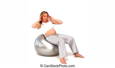 Pregnant woman on a huge gym ball doing exercise