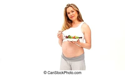 Pregnant woman holding a salad against a white background