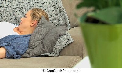 Pregnant woman laying on her couch and she is stroking her...