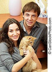 Happy young couple with a cat sitting at home