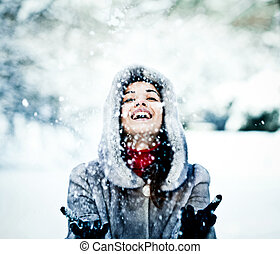 Cute young woman playing with snow in fur coat outdoors
