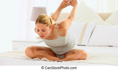 Cute blonde woman stretching herself on her bed
