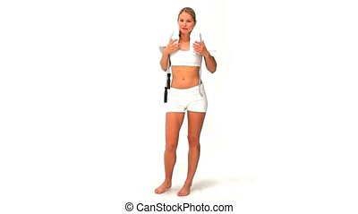 Blonde woman in sportswear with a jump rope and towel...