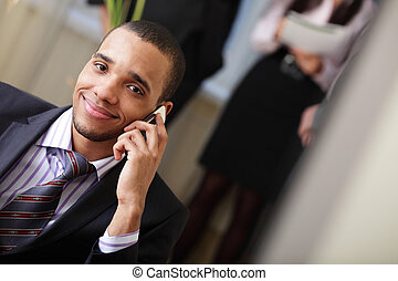 Happy african-american businessman on phone with his team...