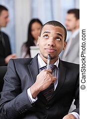 Pensive african-american businessman with his team working...