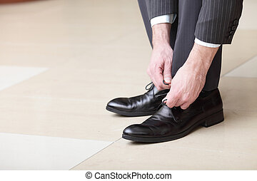 Man ties his shiney new black leather business shoes