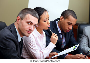 Multi ethnic business team at a meeting. Focus on woman