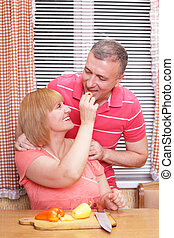 A middle aged woman feeding her husband while preparing meal