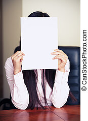 The new worker holds the white blank paper in front of her...